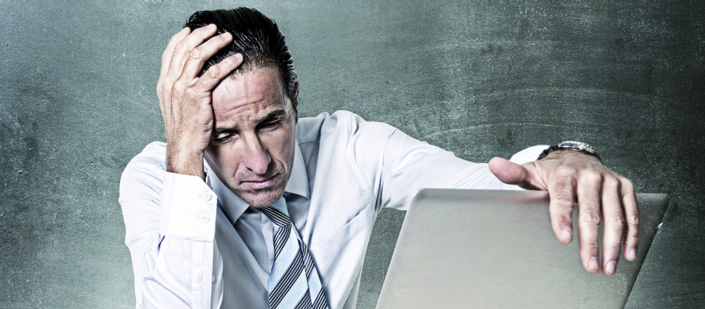 desperate senior businessman in crisis working on computer at of